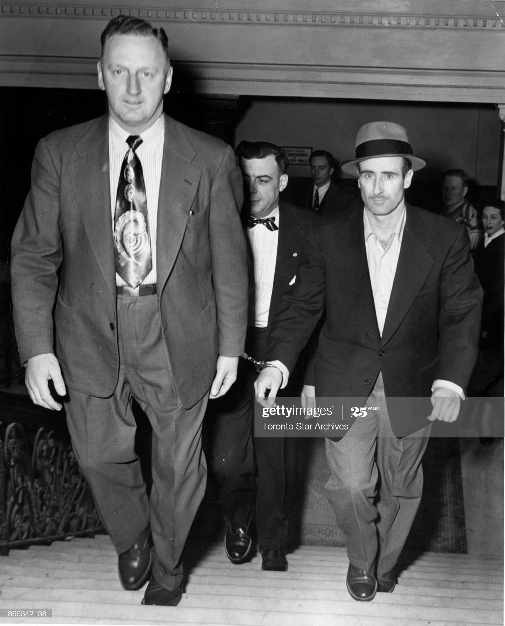 Notorious bank robber Edwin Alonzo Boyd is led into court in 1952 by Det.-Sgt. Adolphus Payne.