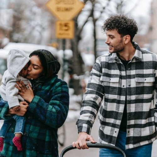 A man and woman dressed in flannel jackets outside on the street with their children during winter.